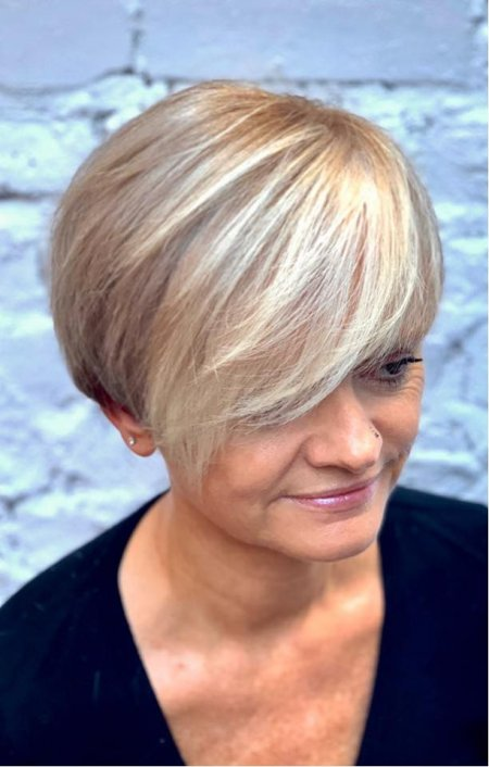 girl sitting on a bench with a blonde fringe and darkblond all over colour on the rest of her hair at the klinik salon London