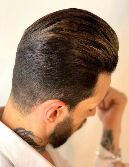 Gents haircut, short skinfade with quiff holding his white shirt with cufflinks done by Anna at the klinik hairdessing London.