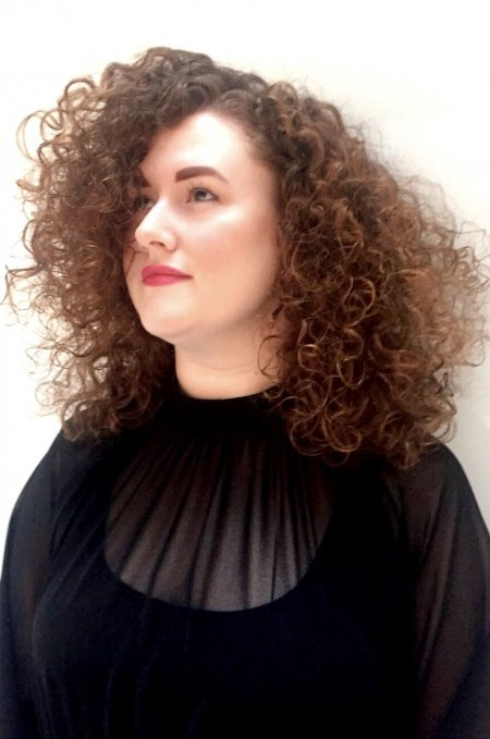 Curly hair has been layered into a shape to volumise the clients curl even further by Mark at the klinik hairdressing London.