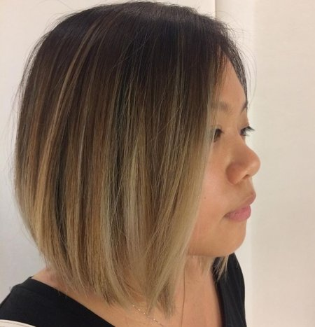 Dark brown hair being coloured with a sombre ombre technique to create a dark to blonde effect throughout the hair with no unwanted tones using Olaplex at the klinik salon London