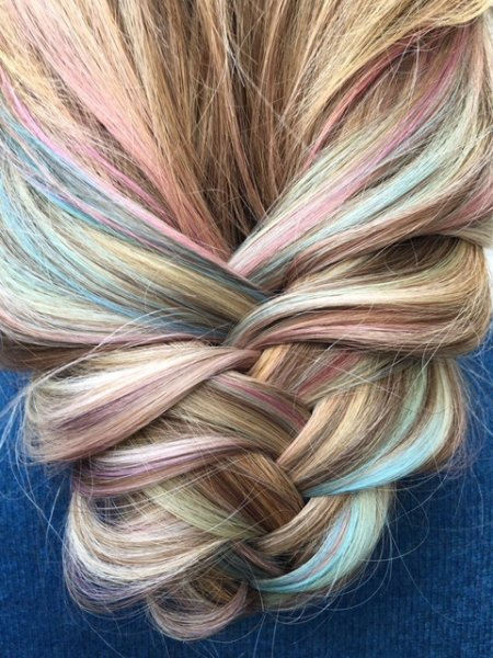 Soft pastel tones running through a loosely plaited hair giving textured finish at the klinik hairdressing Islington