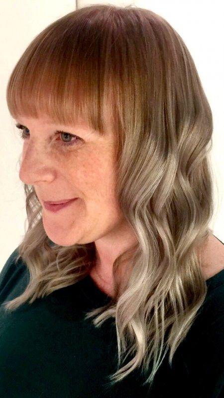 Blond hair being merged by going from a rosegold fringe area to be blended out to a grey silver tone by Mark at the klinik hairdressing Islington.