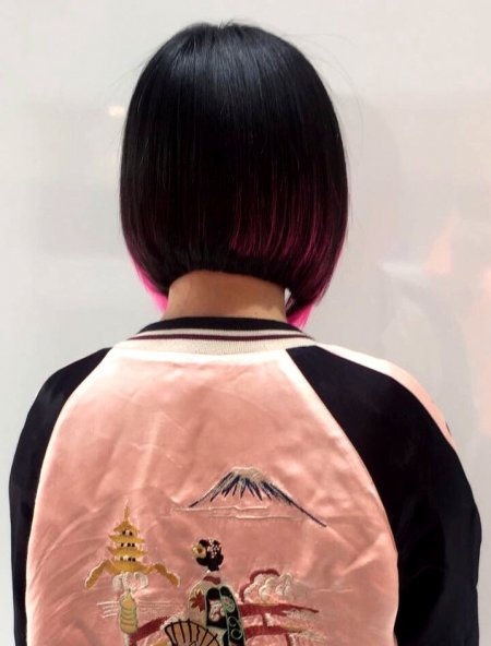 Thick dark hair has been cut into a bob to expose the already there pink bits on the sides done by Mark at the klinik hairdressing London.