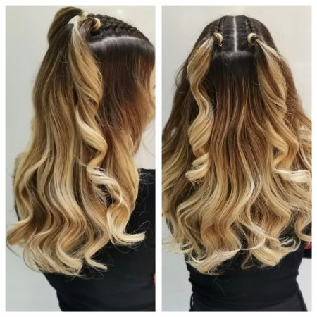 Long blond hair being tonged with loose curls and two plaits on top of the girls head done by Corina at the klinik hairdressing London