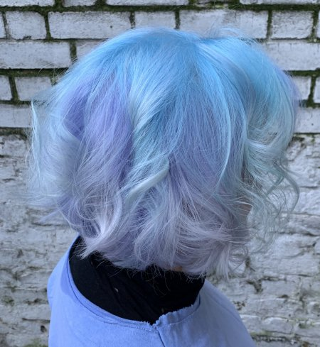 Lady with shouldrlength wavy hair coloured blue in a mix tone like cotton Candy throughout done by Corina at the klinik hairdressing