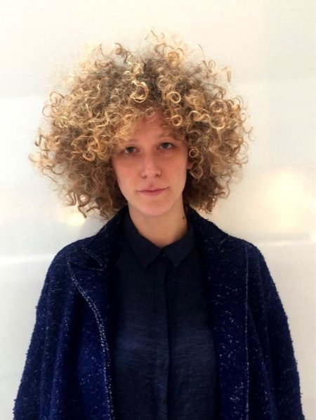 Medium blond hair being cut into a halo shape with large unconected messy curls throughout the hair by Mark at the klinik hairdressing London