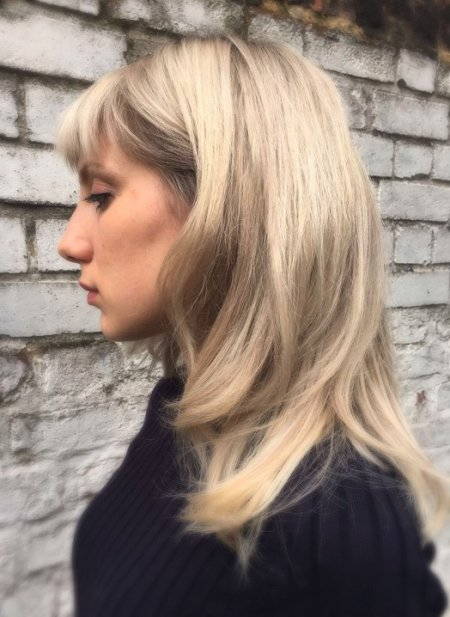 Blonde hair being multitoned by introducing more softe beige colours to create a reverse balayage at the klinik.
