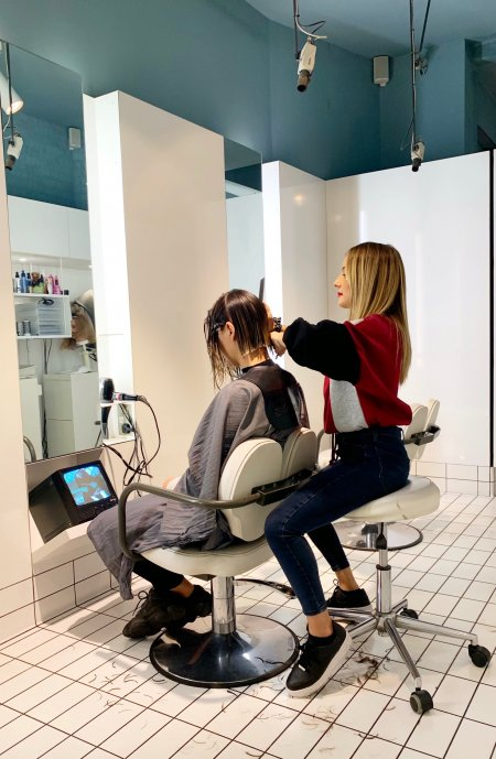 Graduate stylist sitting in a chair cutting a bob for a client as a model at the klinik hairdressing