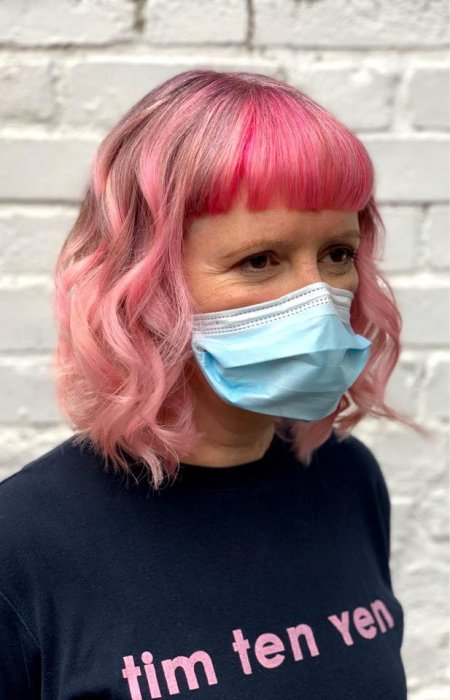 Girl with three shades of pink with a bold fringe wearing a black t-shirt at the klinik salon London
