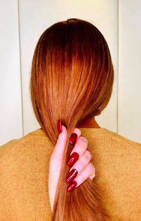 Copper hair with a hand with red nails running through it at the klinik salon London