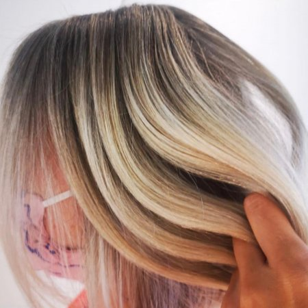 fingers running through a newly coloured blonde hair by Corina at the klinik salon