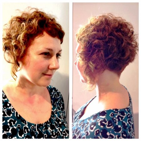 curly hair being cut with a sharp short graduation and wit a lot of texture to bring out the curls