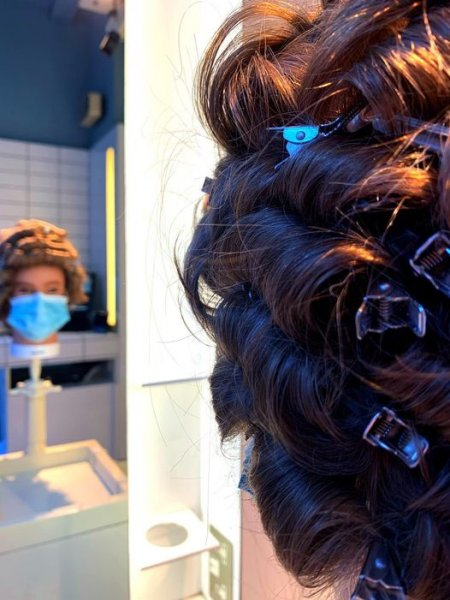 dolls head with pinned hair looking into a mirror at the klinik salon London