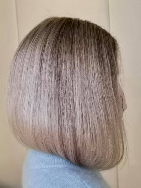 Lady in blue top with icy cool blonde soft graduated bob by Corina at the klinik salon London
