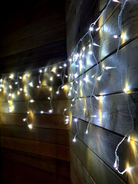 Fairy Lights in a string against a wooden wall in the back garden at the klinik salon London