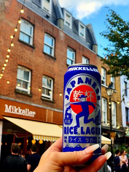 Han holding a japanese rice beer in front of Mikkeller brew pub in Exmouth Market