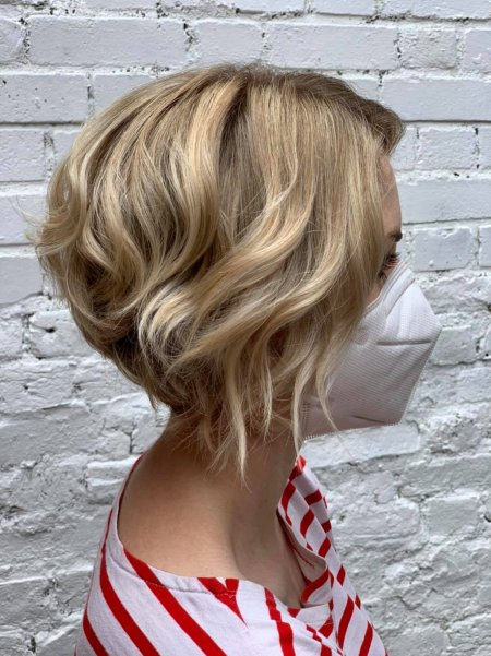 Lady in blonde bob with white and red stripy t-shirt showing off an asymmetric bob at the klinik hairsalon