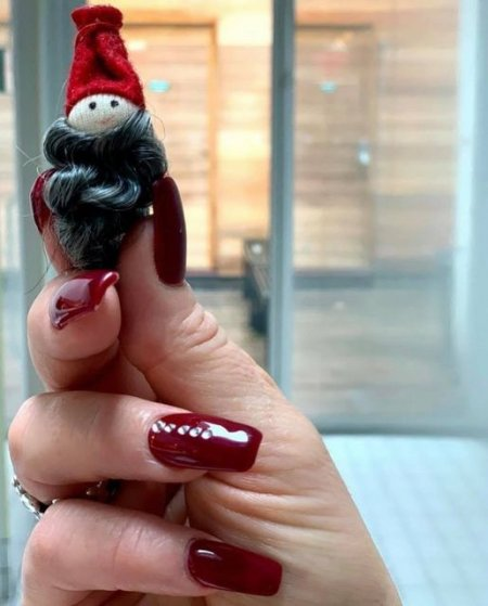 a hand holding a tiny santa revealing its only 12 weeks until Christmas at the klinik salon