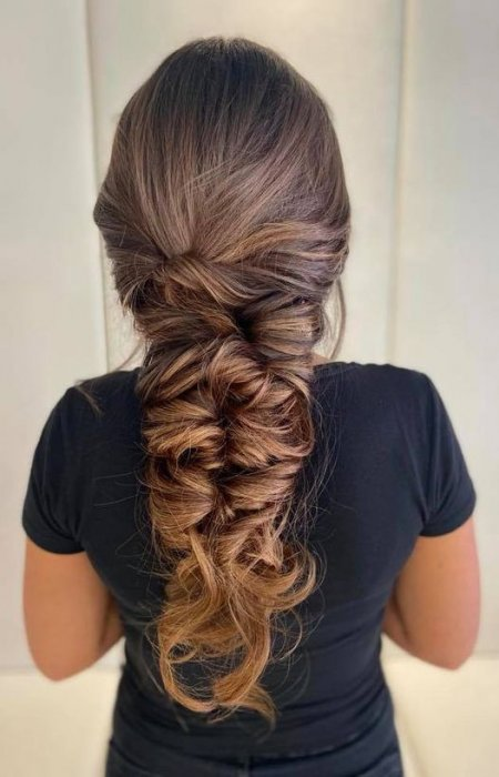 Messy long hsir done up in knots on a girl in a black t-shirt at the klinik salon