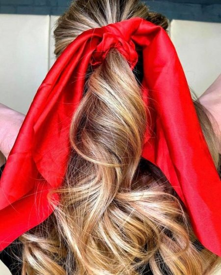 Blonde hair ponytail with large red bow at the klinik salon London