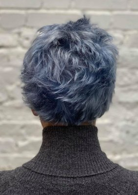 Girl with short blue hair and a grey cardigan at the klinik salon