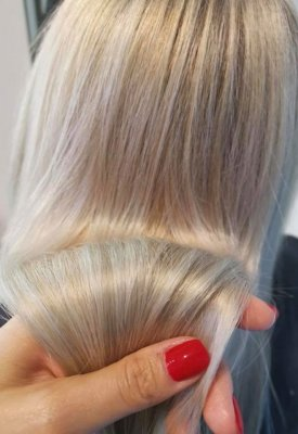 A hand with red nail varnish is holding a newly coloured blond hair at the klinik salon London