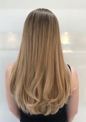 Long natural blonde hair has been coloured with a balayage technique to achieve a sunkissed blond finish. Leyla used pre lighteners with Olaplex to lift and then applied a toner to achieve a soft finish.
