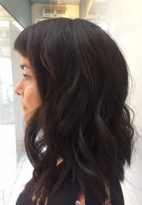 Thick hair being cut into a long shoulder length with a soft graduation at the back at the klinik hairslon London