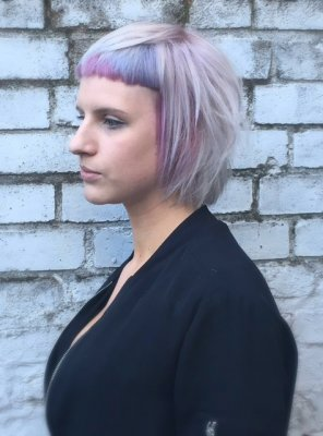 Hair has been cut into a mullet bob with a micro fringe coloured into a subtle lavender in the fringe area at the klinik salon done by Mark