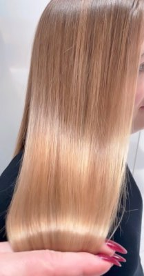 Long hair being moved up and down to show off the ultimate shine with a balayage at the klnik hairdressing