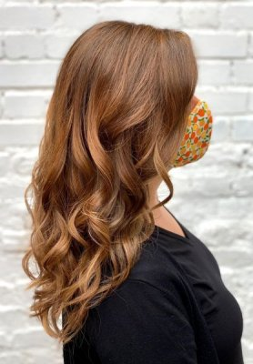An Autumn hair colour on a long hair on a girl wearing a black top and multicoloured face mask against a white wall at the klinik salon London Exmouth Market