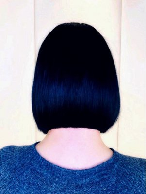 A girl with a blue top and black hair standing with her back to the camera at the klinik salon showing off her bob.