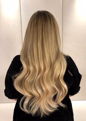 Blonde hair being extended using 120 strands of Easilocks system to give a natural soft long blended look by Leyla at the klinik hairdressing in London