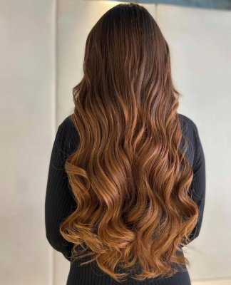 Really long brown hair styled into a soft glam wave with a white background at the klinik salon London