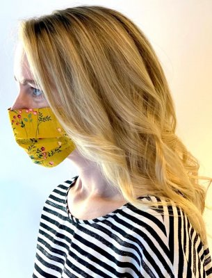 Lady with golden balayage wearing a white and navy top with a yellow face mask at the klinik salon London