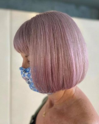 lady with blue face mask having a lavender tone on her hair colour done by Leyla at the klinik salon London
