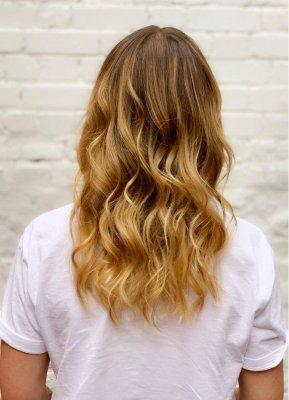 girlin white t-shirt showing off a summer honey blonde balayage done at the klinik salon London