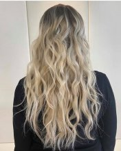 Long blonde hair styled with a mermaid wave by Leyla at the klinik salon London