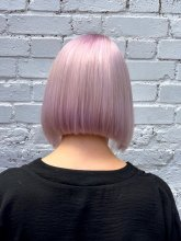 Girl with pink white hair cut into a bob seeing her neck in a black top at the klinik salon London