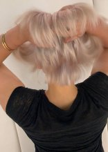 girl running her fingers through her newly coloured blonde hair at the klinik hairdressing in London