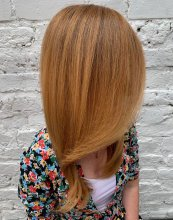Long strawberry blonde hair on a lady in a floral dress at the klinik hairdressing London