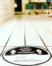 social distancing sign in black and white lying on the floor at the klinik salon advertising we will open on Sundays