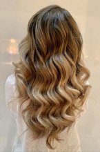 Long blonde hair being curled with soft glamourous waves at the klinik