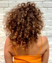 Girl with an orange top and curly hair at the klinik salon