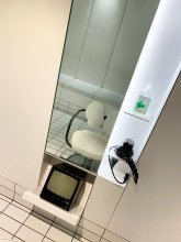 The klinik salon chair getting Covid ready with handsanitiser on mirror stand.
