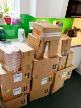 Cardboard boxes standing on the floor in the kitchen to be unpacked from Loreal at the klinik salon