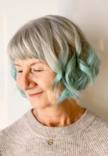 Lady with grey hair adding Schwarzkopf Intant blush Jade on her ends to make her hair look minty green on ends done at the klinik hairdressing.