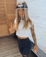 Graduate stylist with face visor at the klinik saying she is back at work