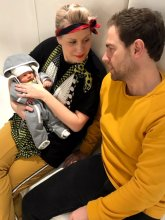 Womn and man sitting on a sofa holding their newborn baby in their arms at the klinik hairdressing London.