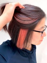 Asian hair being pulled aside to expose a hidden pink colour underneath the temple area done by Anna at the klinik hairdressing in London